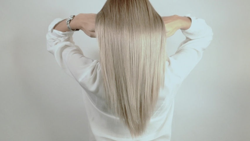 Well-groomed, blond, long hair crumbles on a white background. Hair advertisement. Beautiful blonde hair view from the back. Hair after salon procedures | Shutterstock HD Video #1036764968