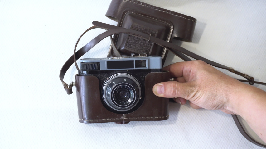 The girl is holding an old film camera. Movement of mechanical parts of the camera. | Shutterstock HD Video #1036766873