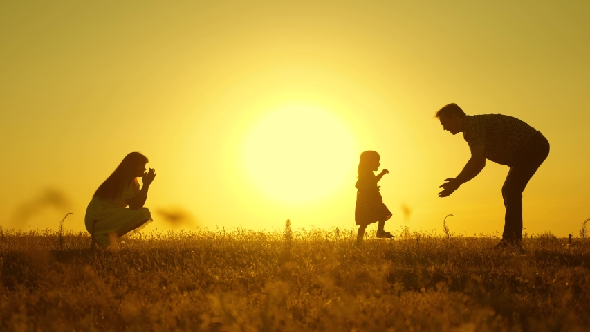 parents play with their little daughter. mother and Dad play with their daughter in sun. happy baby goes from dad to mom. young family in field with a child 1 year. family happiness concept. #1036767440