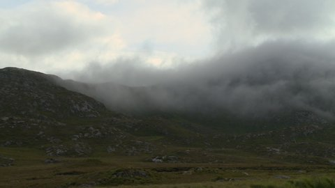 Steady, wide shot of rocky, grassy hills and thick fog.