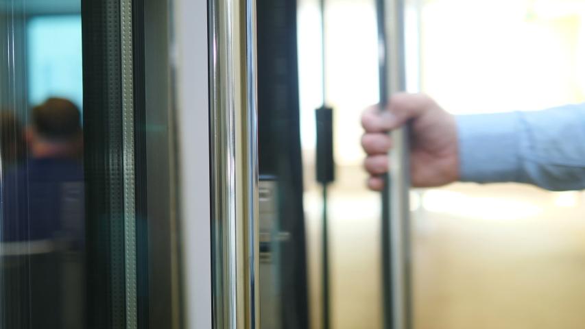 Closeup shot of man opening glass door and entering room and then leaving closing door-handle. Business life concept. man walking through door. 4k