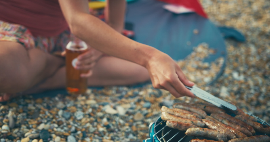 A young mother and her toddler are sitting on the beach and barbecuing sausages | Shutterstock HD Video #1036783682