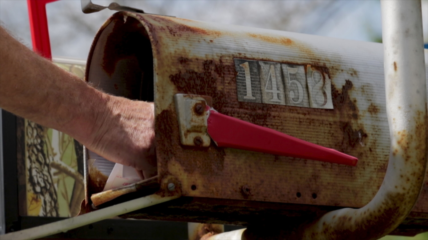 Getting mail form mailbox. Close up man pulling out letters from traditional mailbox at a house. Receiving snail mail letters written by hand. Hand written letters delivered to a mailbox.Communication   Shutterstock HD Video #1036783766
