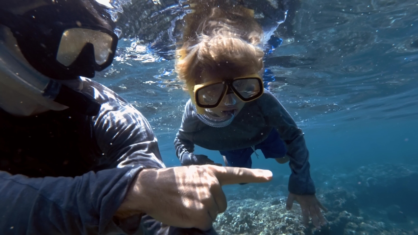 Snorkeling child diving with father in clear blue ocean water with beautiful colorful fishes. Exploring underwater with snorkel, diving mask. Swimming, enjoying adventure in summer vacation