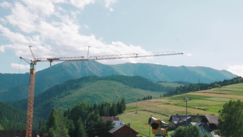 Bachledova / Slovakia - 07 04 2019: ZAKOPANE, POLAND - July 4, 2019: aerial drone shot of a crane in a valley, over the beautiful background of the mountains. | Shutterstock HD Video #1036795439