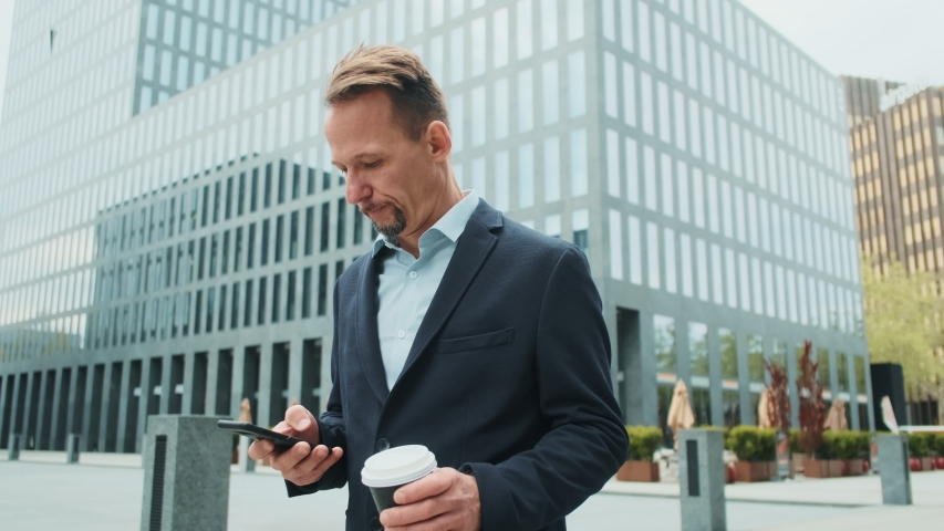 Good looking stylish Caucasian businessman typing while texting a message on the smartphone in the city center with a coffee to-go in hand. Outdoor. | Shutterstock HD Video #1036799843