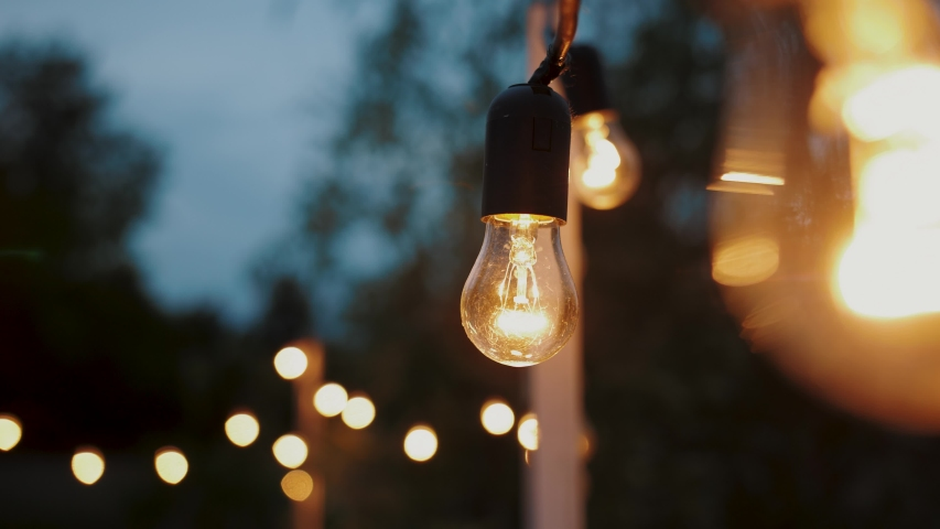 Festival decorative string lights hang and glow outdoors at night. Warm lighting, vintage garland of lamps or glass lantern, electric bulbs shining, decoration for holiday. | Shutterstock HD Video #1036810208