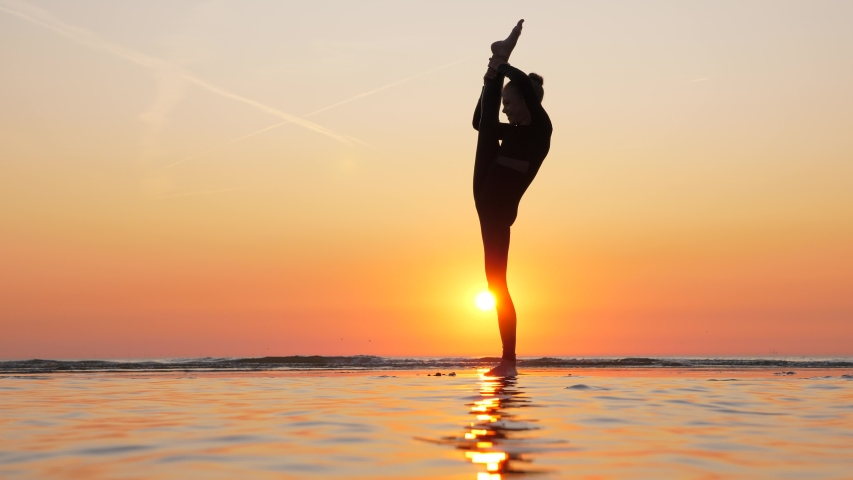 Young gymnast girl show standing split, beautiful silhouette against sunset at sea beach. Professional teenager athlete demonstrate high skill and elegance | Shutterstock HD Video #1036812842