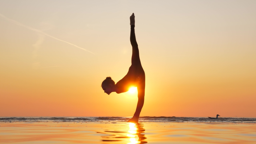Young gymnast perform vertical split, move arms up and stand on one feet. Beautiful silhouetted shot of young elegant girl against vibrant sunset sky. Shallow sea water on foreground. | Shutterstock HD Video #1036812854