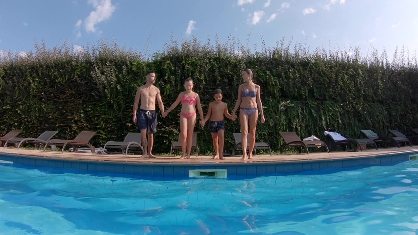 Cheerful family jumping in swimming-pool