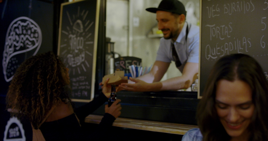 HANDHELD Cheerful waiter taking serving food to customers at counter, Mexican street food truck. 4K UHD RAW graded footage | Shutterstock HD Video #1036816751