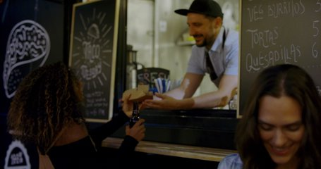 HANDHELD Cheerful waiter taking serving food to customers at counter, Mexican street food truck. 4K UHD RAW graded footage