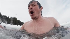 Seamless loopable clip of the young man swimming in the ice hole