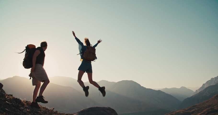 Caucasian couple hiking together with backpacks, helping each other on their way up the mountains - freedom, active lifestyle concept 4k footage | Shutterstock HD Video #1036831193