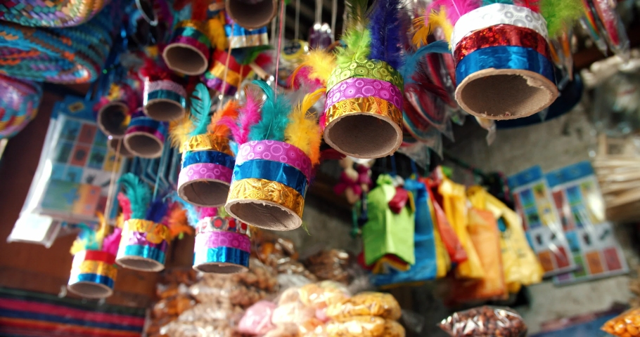 Colorful noise making toy made of feathers and paper, hanging in a traditional Guatemalan fair stand. Street vendor with candies, crafts and toys. Ronron