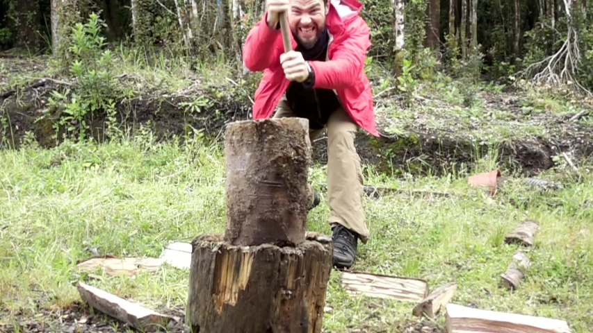 Attractive lumberjack chopping wood with an ax. Slow motion