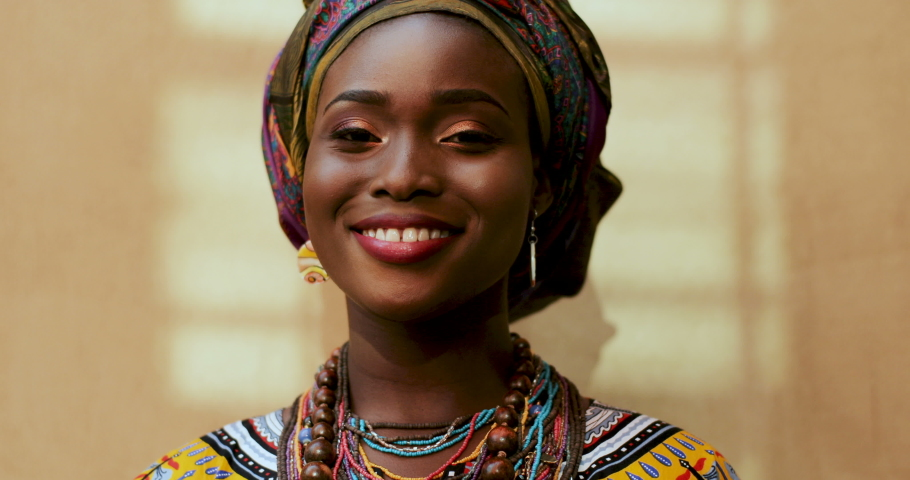 Portrait of African American young charming and happy woman in the scarf on her head and traditional look laughing to the camera. Close up face