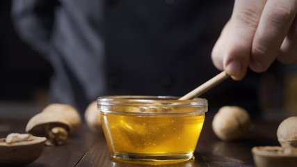 Chef dips wooden honey stick to the glass bowl with liquid honey, cooking with honey, sweet meals with natural ingredients, healthy food, Full HD Prores 422 HQ