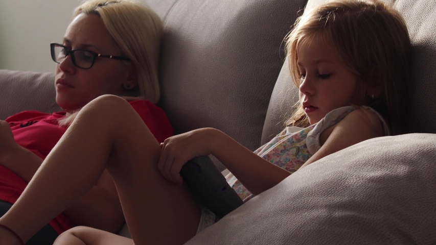 Mom and daughter are sitting, looking at the screen of the tablet and phone | Shutterstock HD Video #1036853699