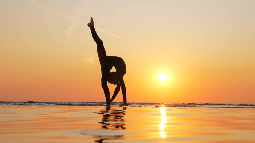 Young gymnast girl elegant silhouette, she stand on one leg in vertical split variation, bend body and use hand to support. Shadow figure against vibrant sunset, sea shore at evening time