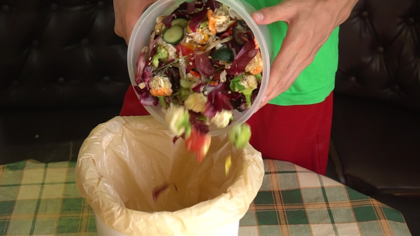 Man throws vegetable peeling, scraps and fruit peels in a compost bucket. Food waste reduce. Sorting of household waste, composting, recycling, zero waste | Shutterstock HD Video #1036865243