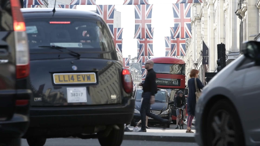 London, United Kingdom - Circa 2019: Pedestrians walking in central London on Regent street in London with Union Jack flags above before Royal Marriage - low angle view through cars and taxis   Shutterstock HD Video #1036872389