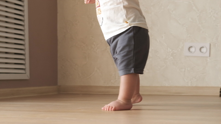 Closeup of baby tiny barefoot legs doing first steps and walking on floor at home without any help. Slow motion