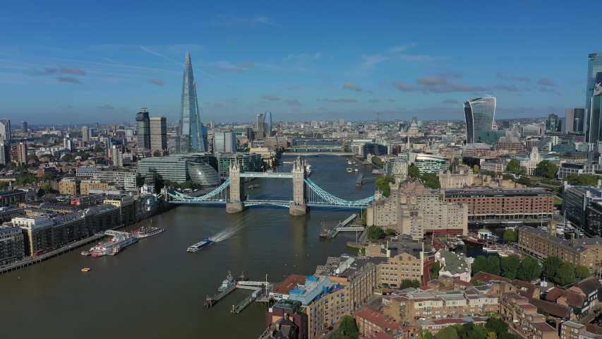 Aerial view of cityscape of London, Tower Bridge and Tower of London, skyscrapers skyline of City of London in background, clear blue sky - panorama of Great Britain from above, United Kingdom, Europe