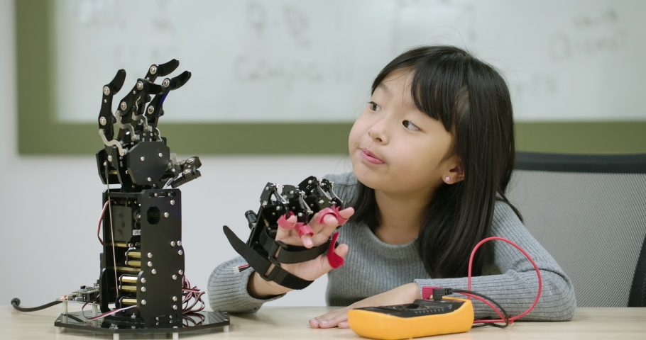 Little asian girl creates movement for mechanical robotic hand in school laboratory. Educational Technology Concept. Royalty-Free Stock Footage #1036878425