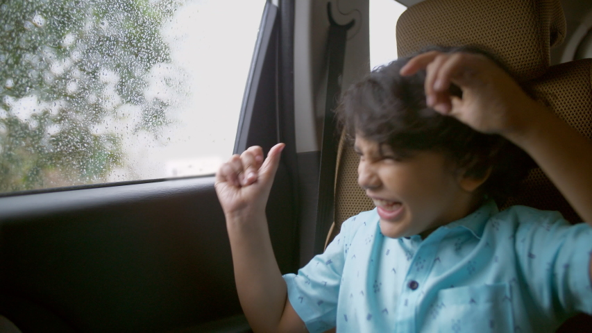 Happy Indian child enjoying music while traveling back home in a car - childhood concept. A handsome young kid listening and dancing to his favorite songs, sitting at the backseat of a car in casua...