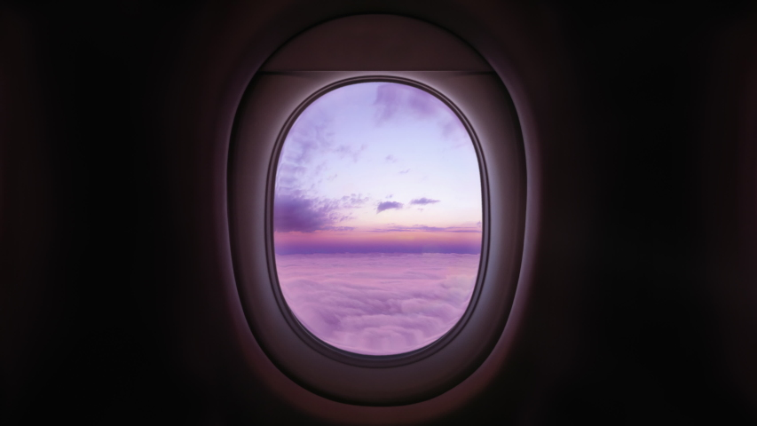 Airplane Window View Above the Clouds at Sunset