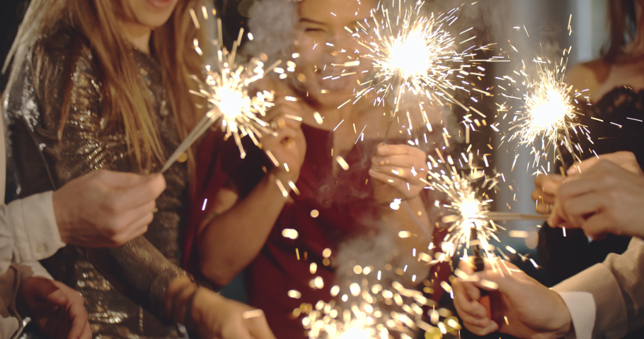 Party fun. Group of friends celebrating night party with fireworks in hand. Glamorous, stylish people enjoying holiday spending together. Friendship, entertainment, diversity, birthday reunion concept