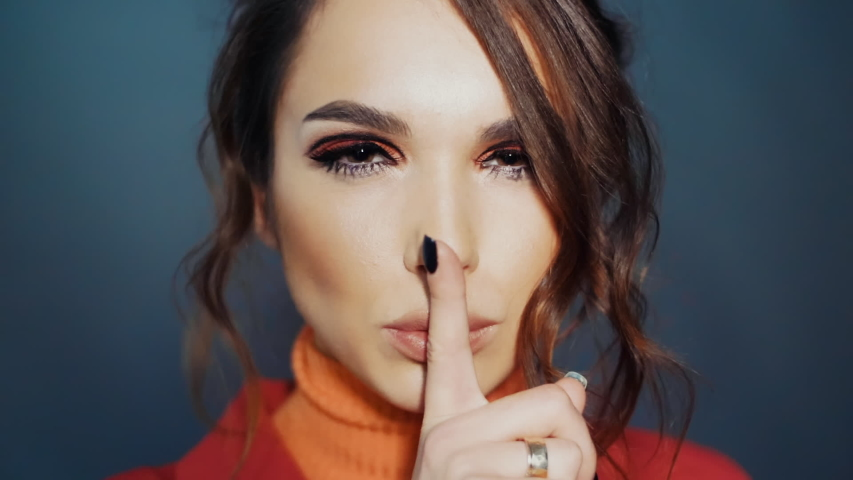 Pretty brunette making sign hush. Beautiful woman showing sign hush holding finger near lips. Sympathetic girl making hush gesture by forefinger. Young woman smiling coquettishly   Shutterstock HD Video #1036899725