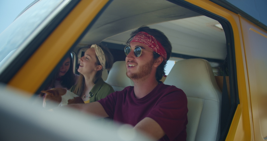Best happy friends traveling with puppy dog in vintage camper van wearing trendy clothes, Enjoying Adventure Road Trip Vacation Friendship Concept, Cheerful friends traveling in Europe Van Life | Shutterstock HD Video #1036901633