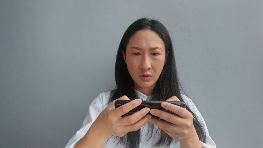 Angry Gamer Concept. Asian women gamer is playing Game on Mobile Smart Phone. | Shutterstock HD Video #1036910906