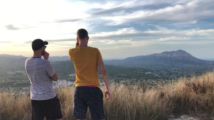 Back view of two young men standing at the top of the hill. Tourist pointing to some spot. View after hiking. Beautiful tropical mountain in Spain during the sunset - slow motion.  | Shutterstock HD Video #1036921361