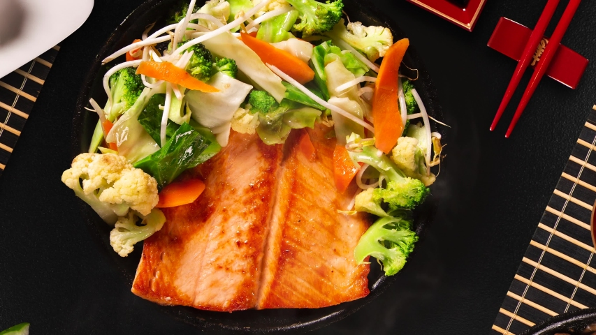 Delicious Teppanyaki Salmon grill food with vegetable in the iron pan with smoke. Top view. | Shutterstock HD Video #1036926995