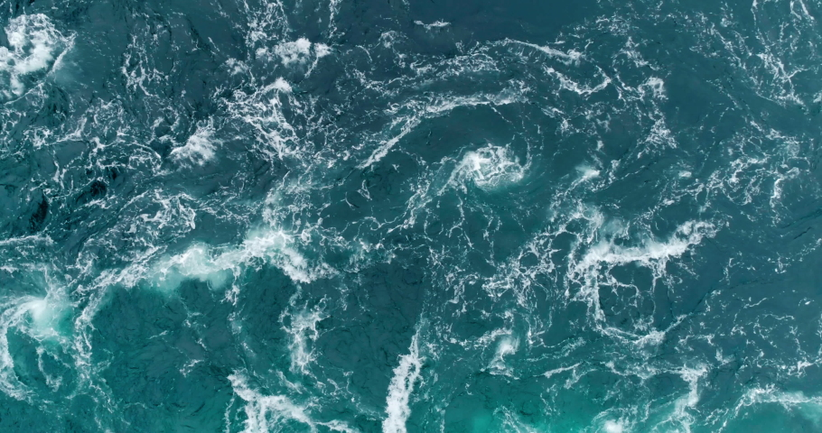 4K drone video with birds-eye view of the abstract and powerful water currents, rapids and whirlpools of the worlds larges maelstrom Saltstraumen in Bodø, Norway. Royalty-Free Stock Footage #1036929431