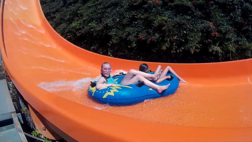Girls sliding on water slide in amusement aquapark at summer vacation. People having fun riding on slides in outdoor water park at holiday