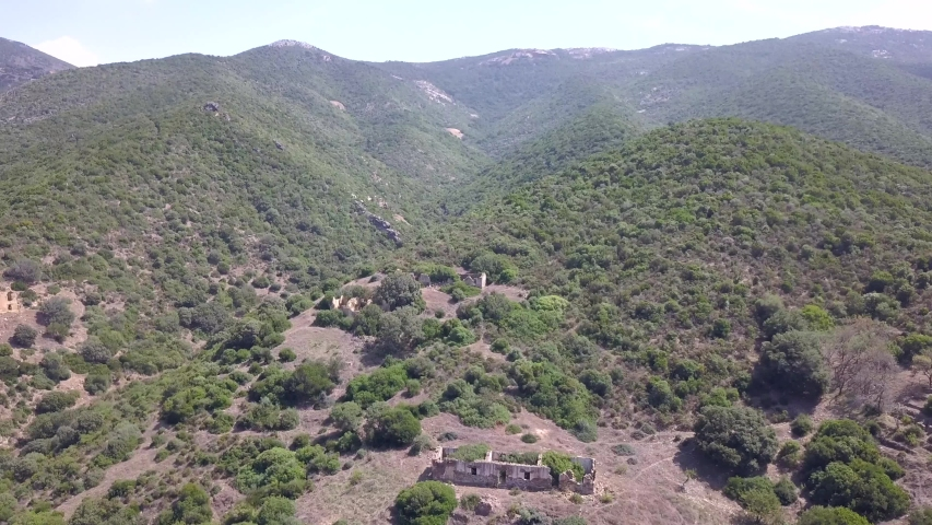 Drone aerial shot over a green hill landscape in the mediterranean countryside of Sardinia.The shot is tilting down to the ruins of an abandoned building now populated by vegetation, plants and trees, | Shutterstock HD Video #1036938635