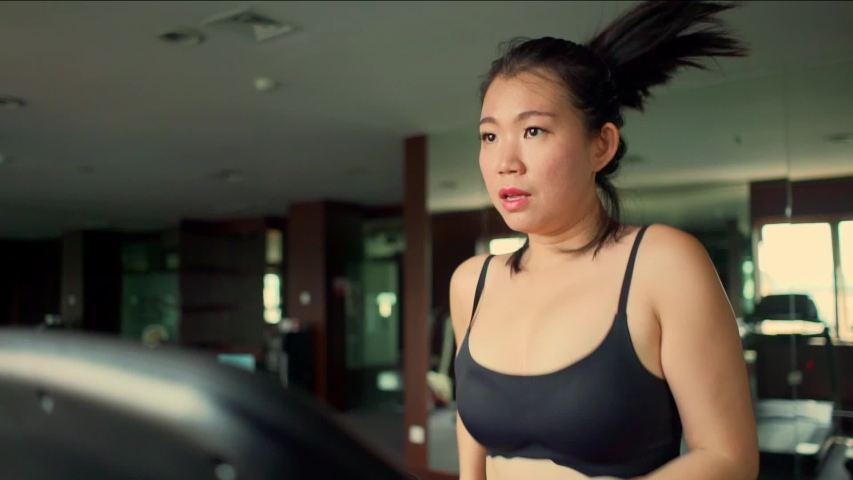 Young attractive and cute Asian Korean woman doing running workout at hotel gym or fitness club jogging in treadmill training hard in healthy lifestyle and body care concept  | Shutterstock HD Video #1036941608