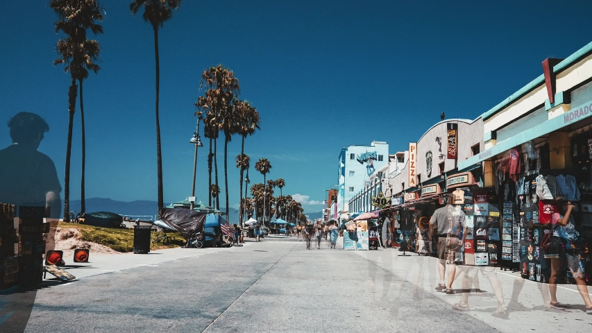 Los Angeles, USA. May 10, 2019. Vintage time lapse view of the Venice beach in California, LA. People walking down the Venice beach broadway near palms and blue skies on a sunny day. Retro style.