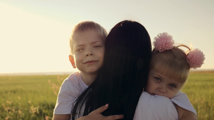 A happy family. A young mother hugs her two young children, laughing in a field in the sun at sunset. Family love concept | Shutterstock HD Video #1036945808