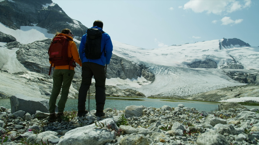 Lake view Heli hikers male and female young Caucasian travelers hiking in scenic mountains near ice glacier RED MONSTRO | Shutterstock HD Video #1036970354