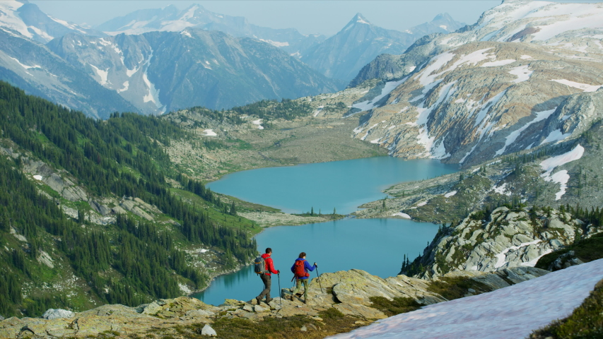 Young adventurous male female Heli hikers Caucasian tourists viewing glacial mountain lake in summer Canada British Columbia RED MONSTRO
