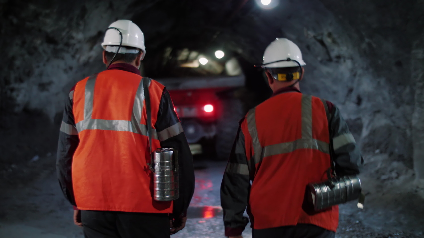 Two workers with helmets and equipment walking through a mine tunnel, in a background of heavy mining machinery. Royalty-Free Stock Footage #1036970852