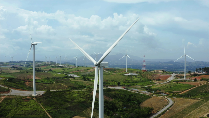 Aerial view, windmills rotating by the force of the wind and generating clean renewable energy for sustainable development in green ecologic way on cloudy sky at highland. Panorama curve shot by drone | Shutterstock HD Video #1036976843