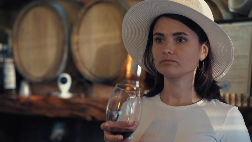 A girl in a white hat tastes red wine in a wine cellar. Girl drinking red wine, old barrels in the background. #1036981088