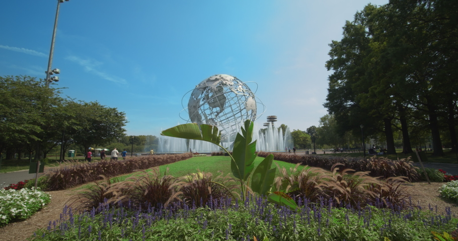 Queens, New York / United States - July 26 2019: The Unisphere from the 1964 Worlds fair in Flushing Meadow park. Pan up from flower garden.