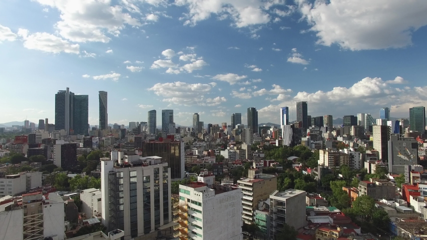 Aerial panoramic view of the skyline in Reforma Avenue, in Mexico City, on a clear day with blue sky. Drone slowly flying forward